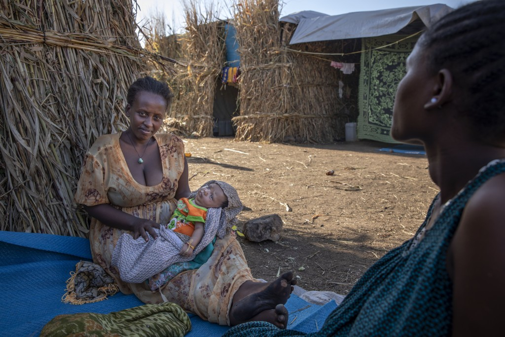 Lemlem Haylo Rada, 25, who fled the conflict in Ethiopia's Tigray region, holds her one-month old baby in front of her shelter, at Um Rakuba refugee c...