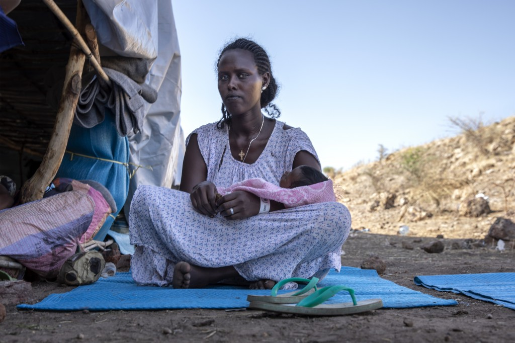 Terhas Tsfa, 25, who gave birth on a street as she fled the conflict in Ethiopia's Tigray region, holds her baby at Um Rakuba refugee camp in Qadarif,...