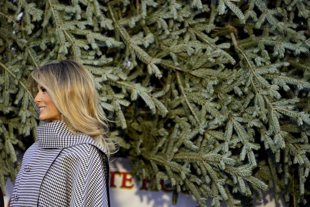 First lady Melania Trump stands next to the 2020 Official White House Christmas tree as it is presented on the North Portico of the White House, Monda...