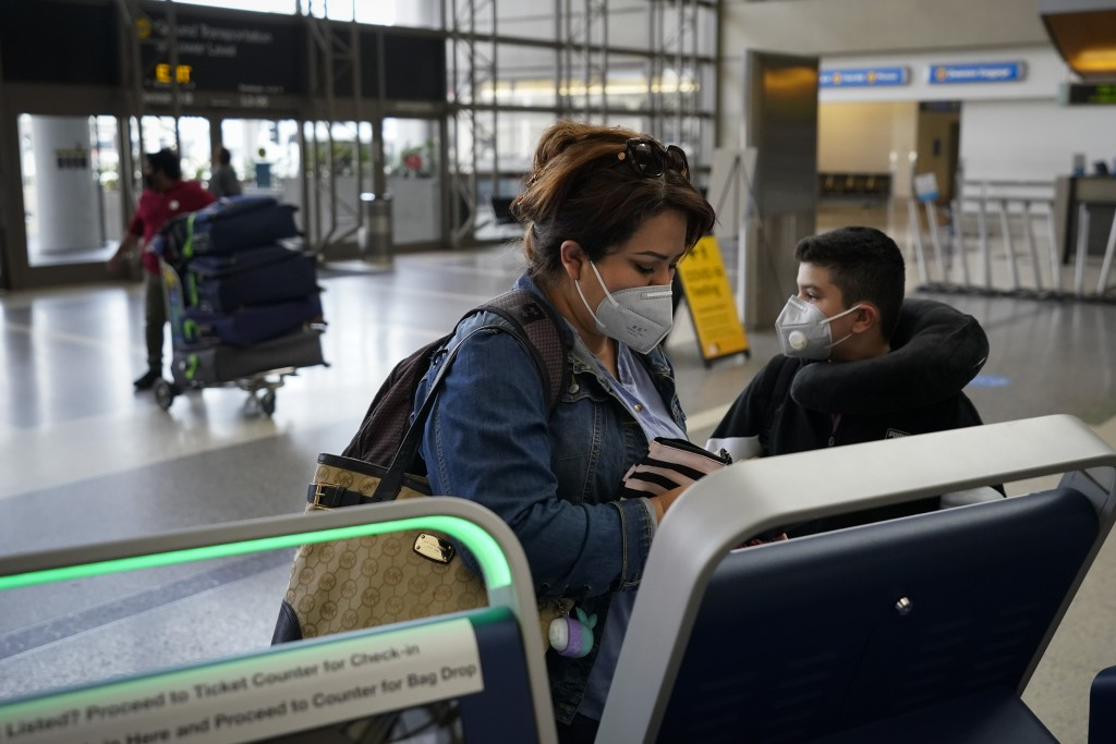 Esmeralda Elizalde checks in for her flight to Mexico at the Los Angeles International Airport in Los Angeles, Monday, Nov. 23, 2020. About 1 million ...