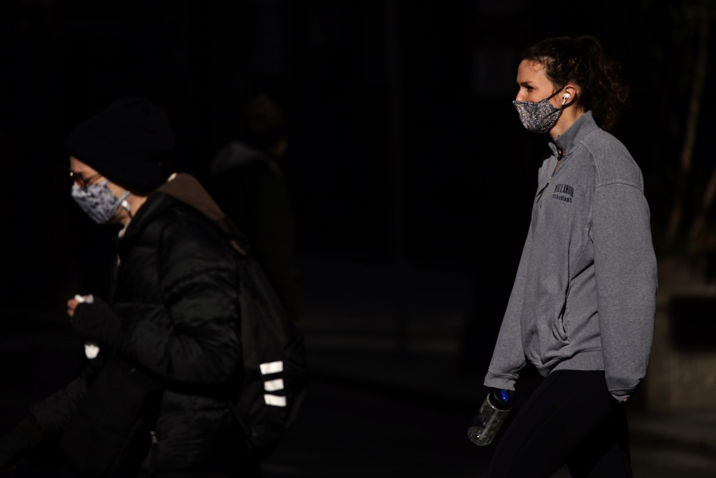 In this Nov. 18, 2020 photo, people wearing face masks cross Broad Street in Philadelphia. As governors and mayors grapple with an out-of-control pand...