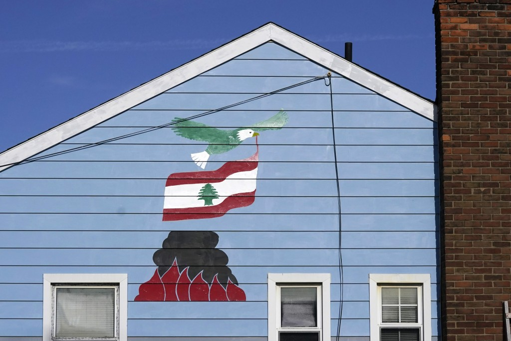 A bald eagle flying with the Lebanon flag over the Beirut port blast is depicted on Samih Zreik's house, Thursday, Nov. 19, 2020, in Dearborn, Mich. Z...