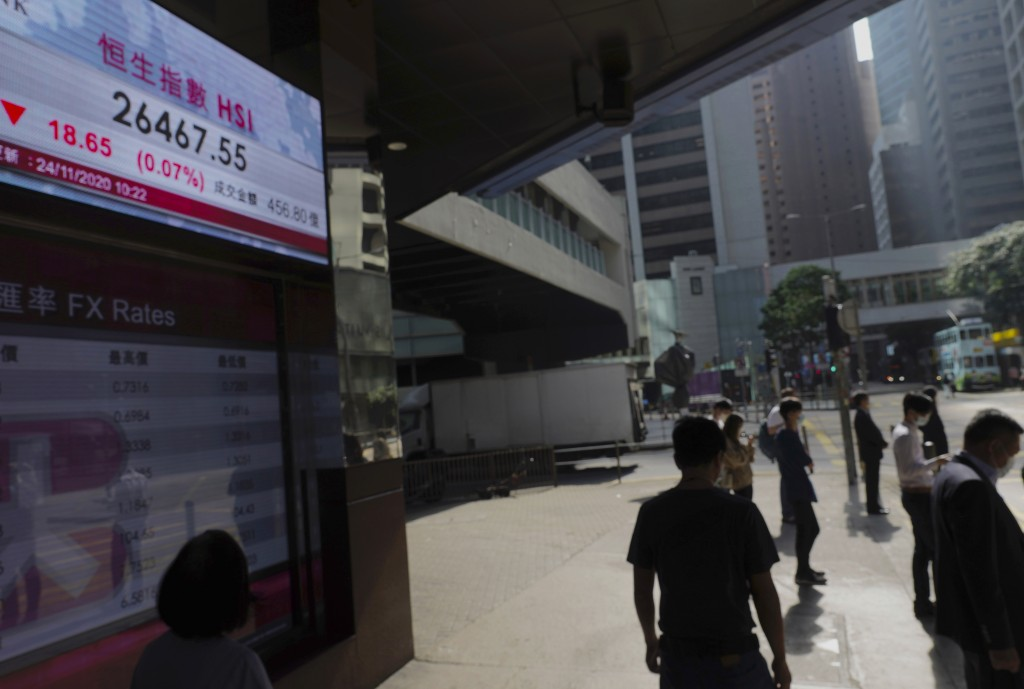 People walk past a bank's electronic board showing the Hong Kong share index at Hong Kong Stock Exchange Tuesday, Nov. 24, 2020. Asian shares were mos...
