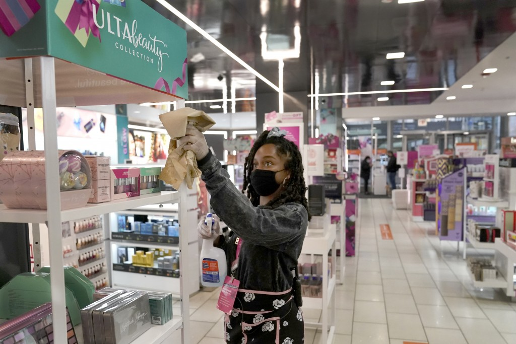 Tamia Prescott sanitizes a cosmetic display Thursday, Nov. 19, 2020, at an Ulta beauty store on Chicago's Magnificent Mile. (AP Photo/Charles Rex Arbo...