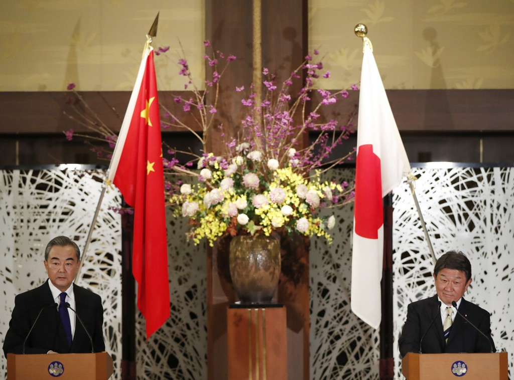 China' Foreign Minister Wang Yi, left, and his Japanese counterpart Toshimitsu Motegi participate in a press briefing in Tokyo on Tuesday, Nov. 24, 20...