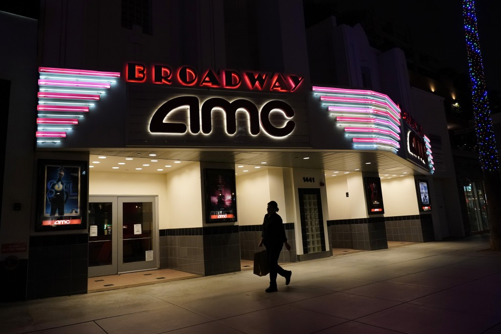 FILE - In this Thursday, Nov. 19, 2020 file photo, a shopper walks past a closed AMC movie theater in Santa Monica, Calif. Despite the expected arriva...