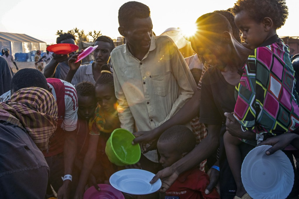 Tigray refugees who fled the conflict in Ethiopia's Tigray region, wait to get cooked rice served by Sudanese local volunteers at Um Rakuba refugee ca...