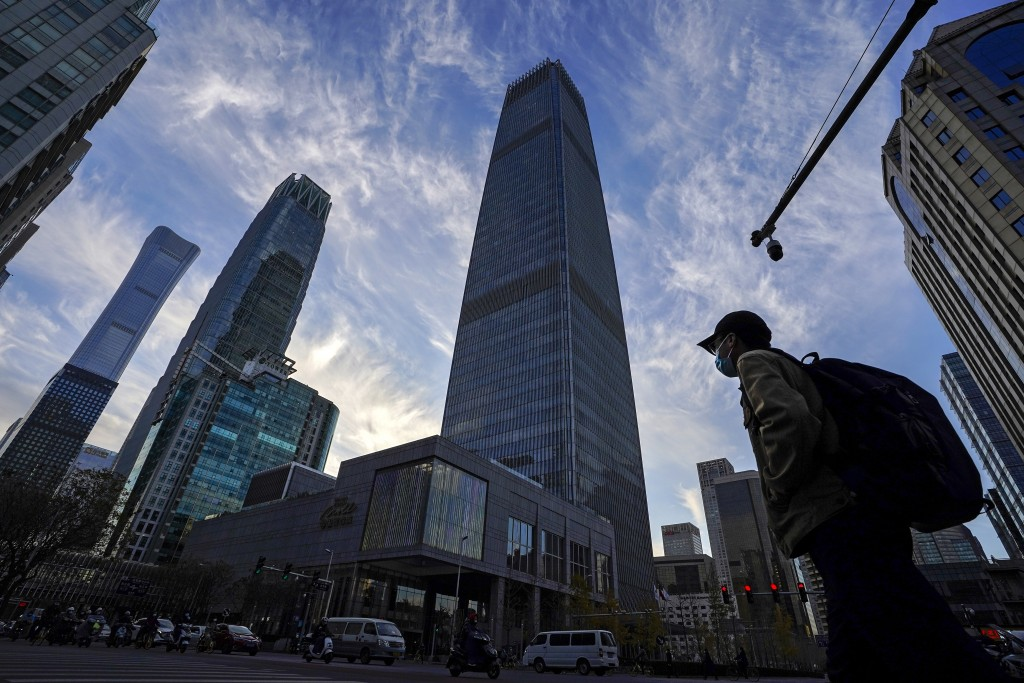 A man wearing a face mask and motorists pass through the skyscrapers at the Central Business District in Beijing, Tuesday, Nov. 24, 2020. China has re...