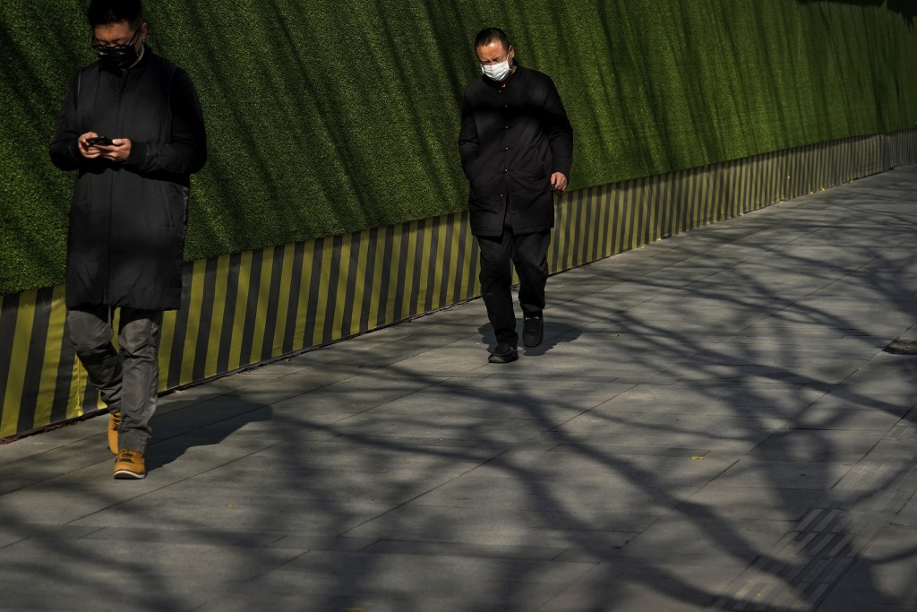 People wearing face masks to help curb the spread of the coronavirus walk by tree shadows at the Central Business District in Beijing, Tuesday, Nov. 2...