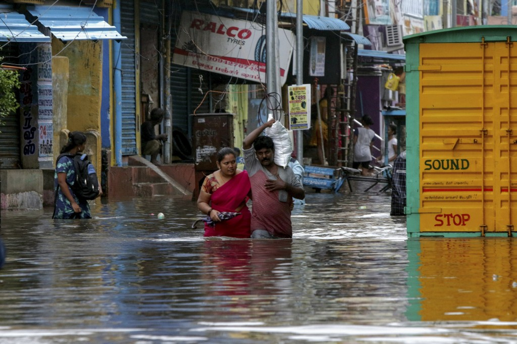 People wade through a flooded street in Chennai, India, Wednesday, Nov.25, 2020. India's southern state of Tamil Nadu is bracing for Cyclone Nivar tha...