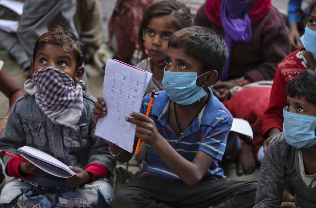 Underprivileged children wearing face masks as a precaution against the coronavirus attend a class at the Sangharsh Vidya Kendra school at a slum area...