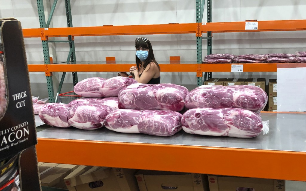 A shopper in a face mask looks over cuts of beef piled up in a cold room for purchase at a Costco warehouse store Tuesday, May 5, 2020, in west Denver...