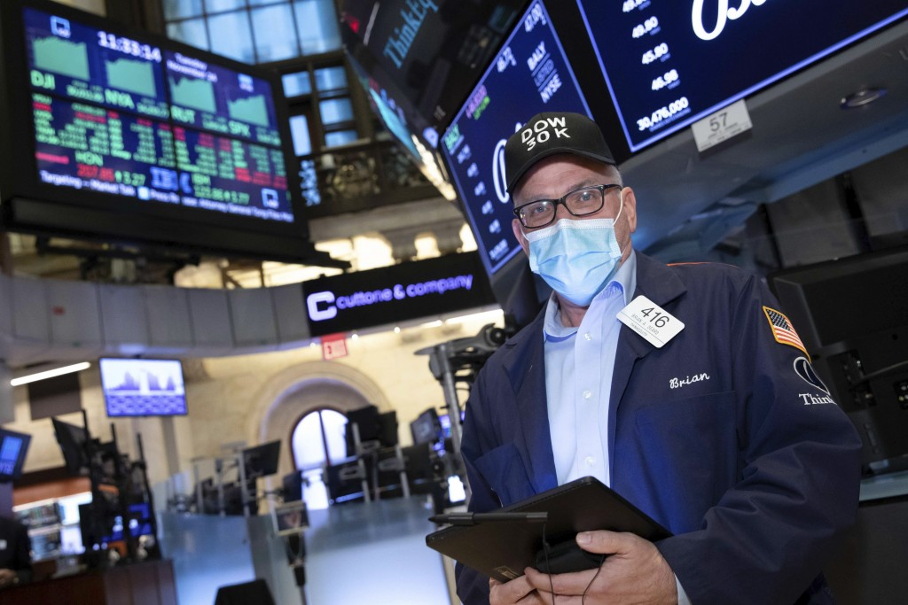 A trader works at the New York Stock Exchange, Tuesday, November 24, 2020. The Dow Jones Industrial Average traded above 30,000 points for the first t...