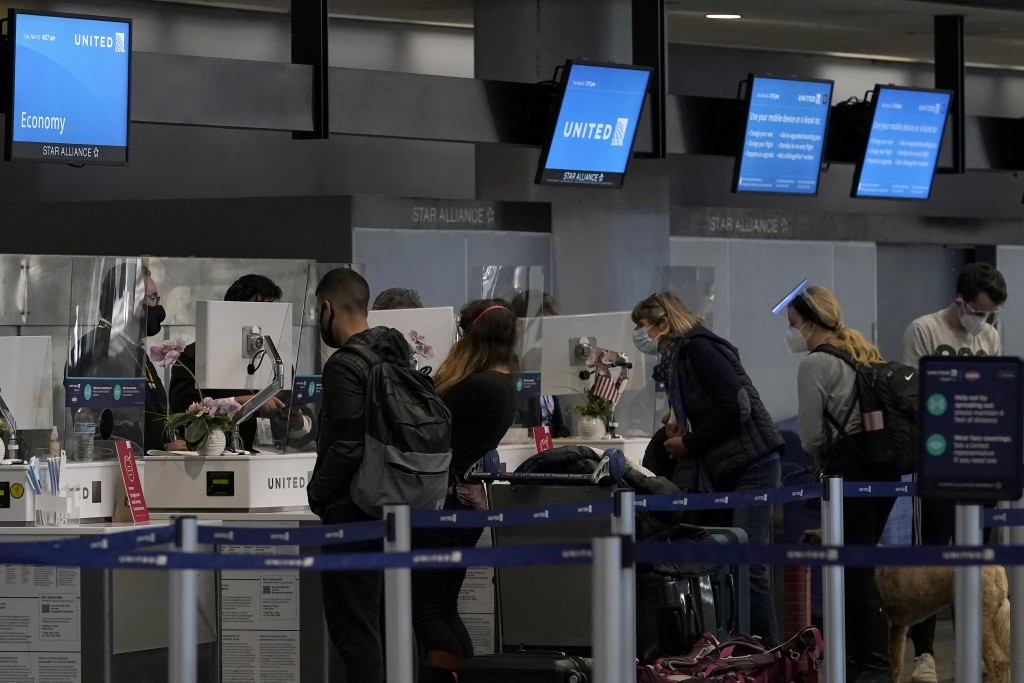Travelers wearing masks check in at United desks at San Francisco International Airport during the coronavirus outbreak in San Francisco, Tuesday, Nov...