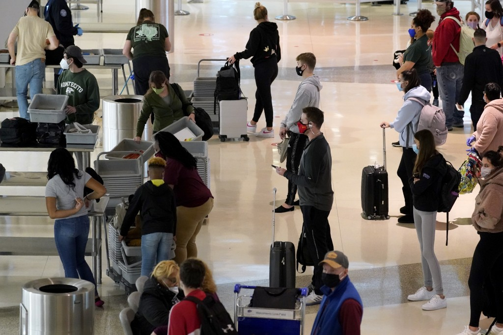 Air travelers line up to go through a a security checkpoint at Love Field Airport in Dallas, Tuesday, Nov. 24, 2020. (AP Photo/Tony Gutierrez)