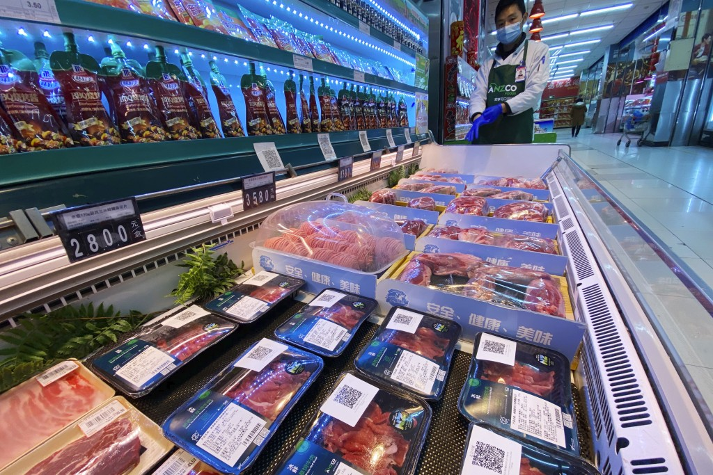 A worker wearing a mask and gloves stand near beef products from New Zealand packaged with a QR-code linked to its coronavirus test results displayed ...