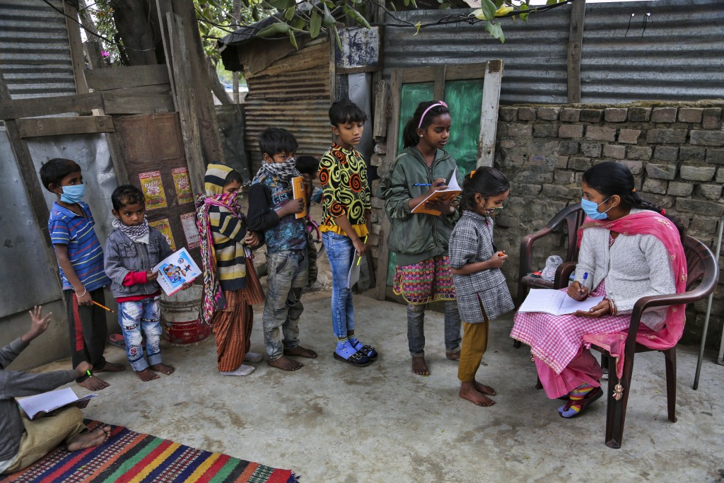 A teacher wearing face mask as a precaution against the coronavirus checks the note books of children at the Sangharsh Vidya Kendra school at a slum a...