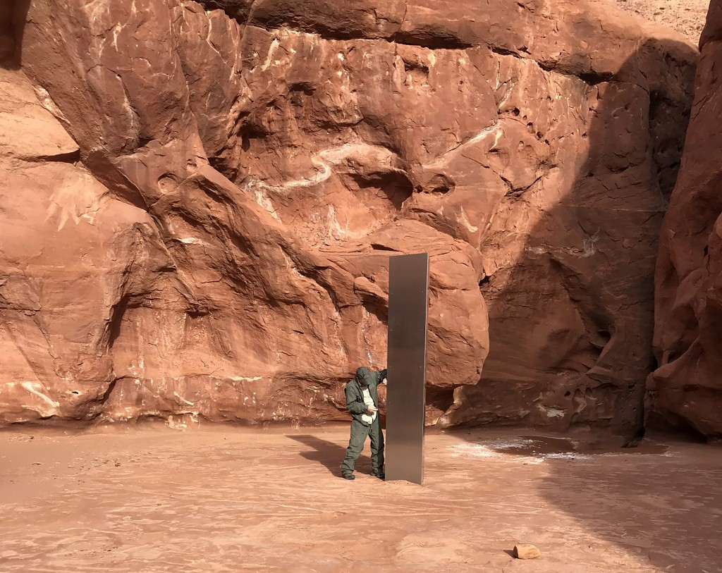 This Nov. 18, 2020 photo provided by the Utah Department of Public Safety shows a Utah state worker inspecting a metal monolith that was found install...