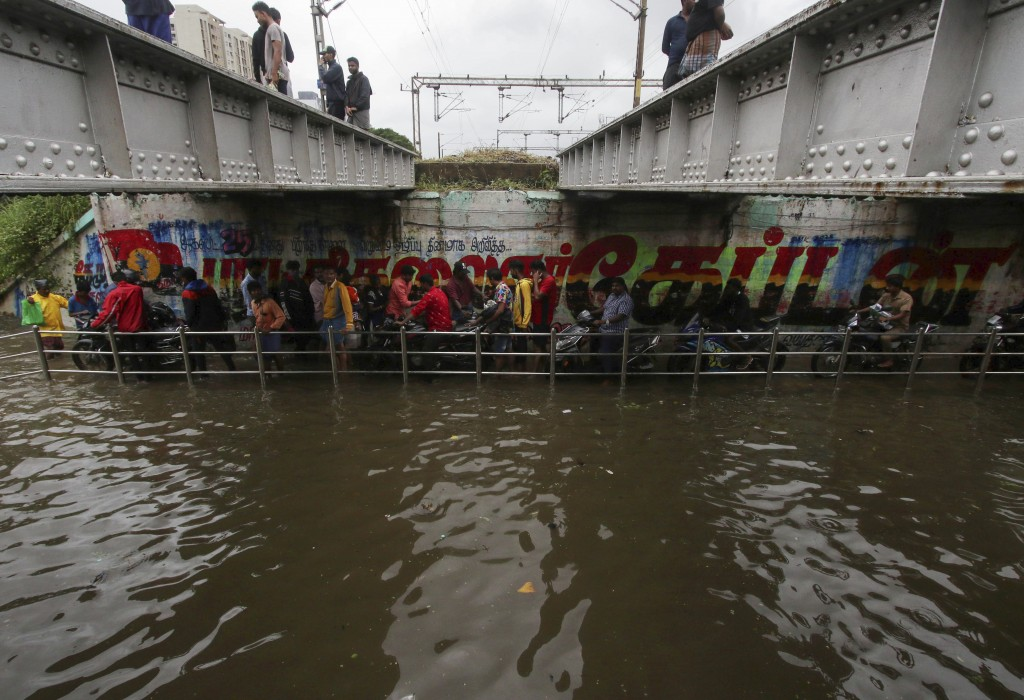 People make their way through a flooded underpass in Chennai, India, Wednesday, Nov.25, 2020. India's southern state of Tamil Nadu is bracing for Cycl...
