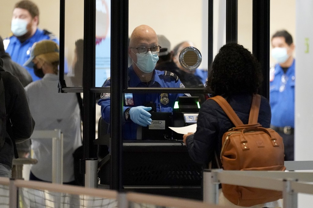 A TSA agent assist a travel at a security checkpoint at Love Field Airport in Dallas, Tuesday, Nov. 24, 2020. (AP Photo/Tony Gutierrez)