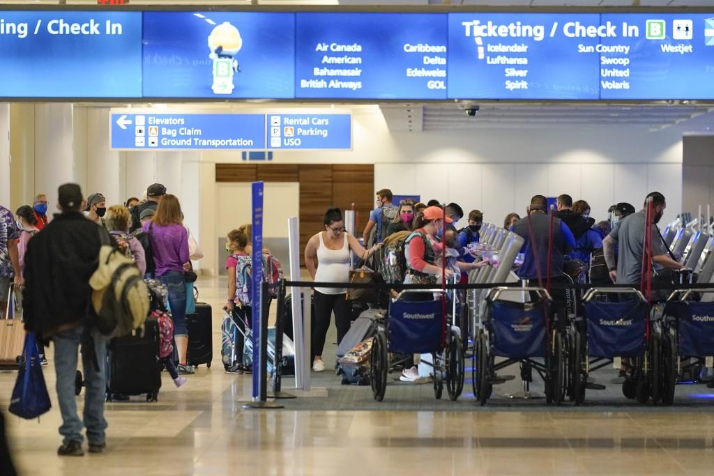 Holiday travelers check in at kiosks near an airline counter at Orlando International Airport Tuesday, Nov. 24, 2020, in Orlando, Fla. (AP Photo/John ...