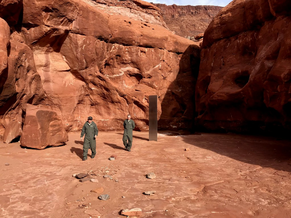 This Nov. 18, 2020 photo provided by the Utah Department of Public Safety shows Utah state workers walking near a metal monolith in the ground in a re...