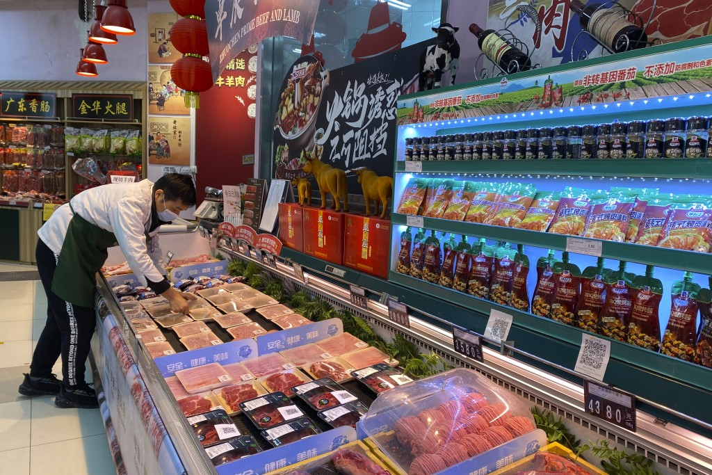 A worker wearing a mask handles meat products including beef from New Zealand packaged with a QR-code linked to its COVID test results at a supermarke...