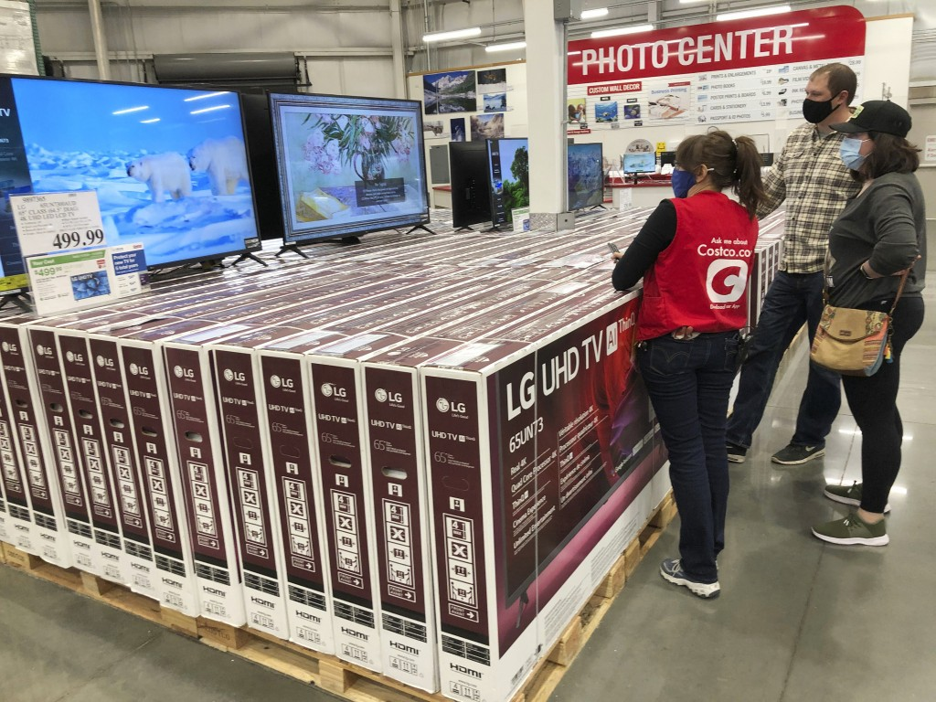 A sales associate helps customers as they consider the purchase of a big-screen television at a Costco warehouse on Wednesday, Nov. 18, 2020, in Sheri...