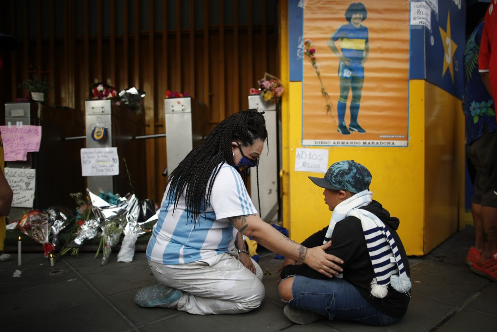 Fans mourn under a poster of Diego Maradona at the entrance of the Boca Juniors stadium, known as La Bombomera, in Buenos Aires, Argentina, Wednesday,...