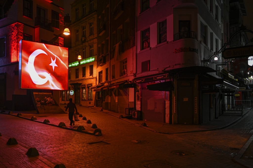 A man walks in Istanbul, late Wednesday, Nov. 25, 2020. The number of daily COVID-19 infections in Turkey jumped to above 28,000 on Wednesday after, i...