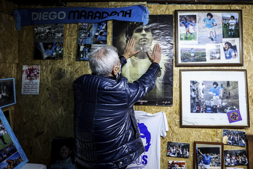 A man touches a poster of soccer legend Diego Maradona, in Naples, Italy, Wednesday, Nov. 25, 2020. Diego Maradona has died. The Argentine soccer grea...