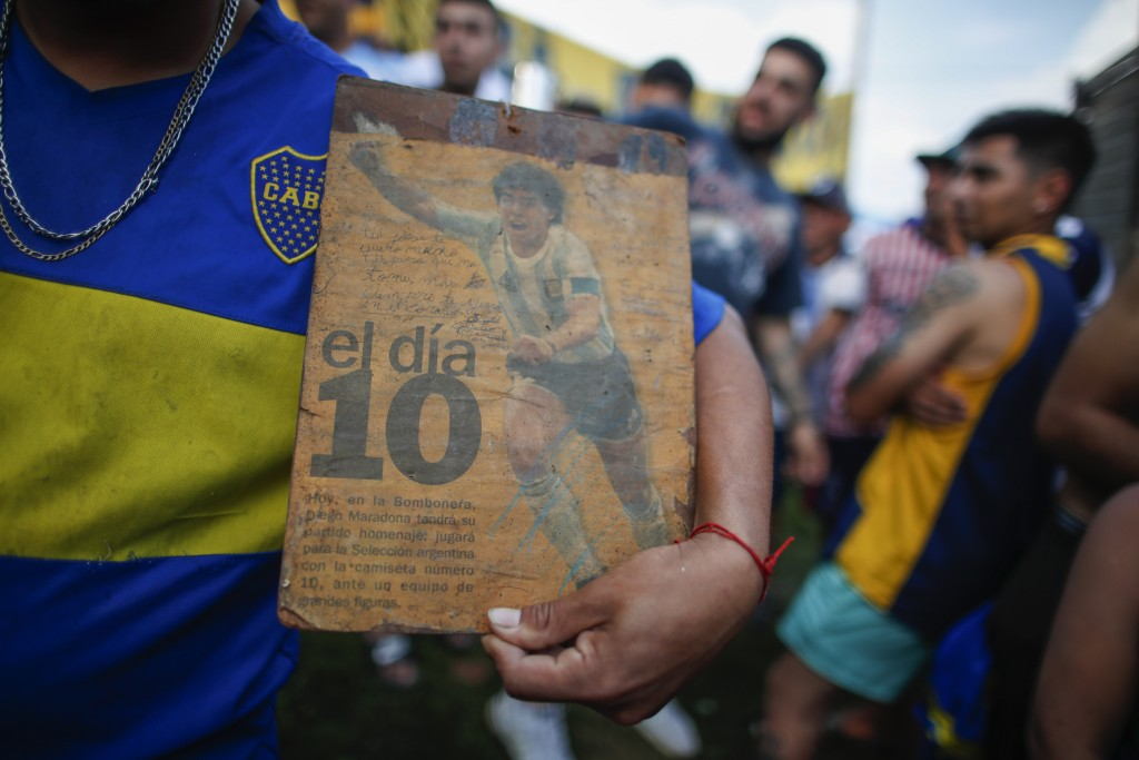 Neighbors gather in front of the house where Diego Maradona was born in the Villa Fiorito neighborhood of Buenos Aires, Argentina, Wednesday, Nov. 25,...