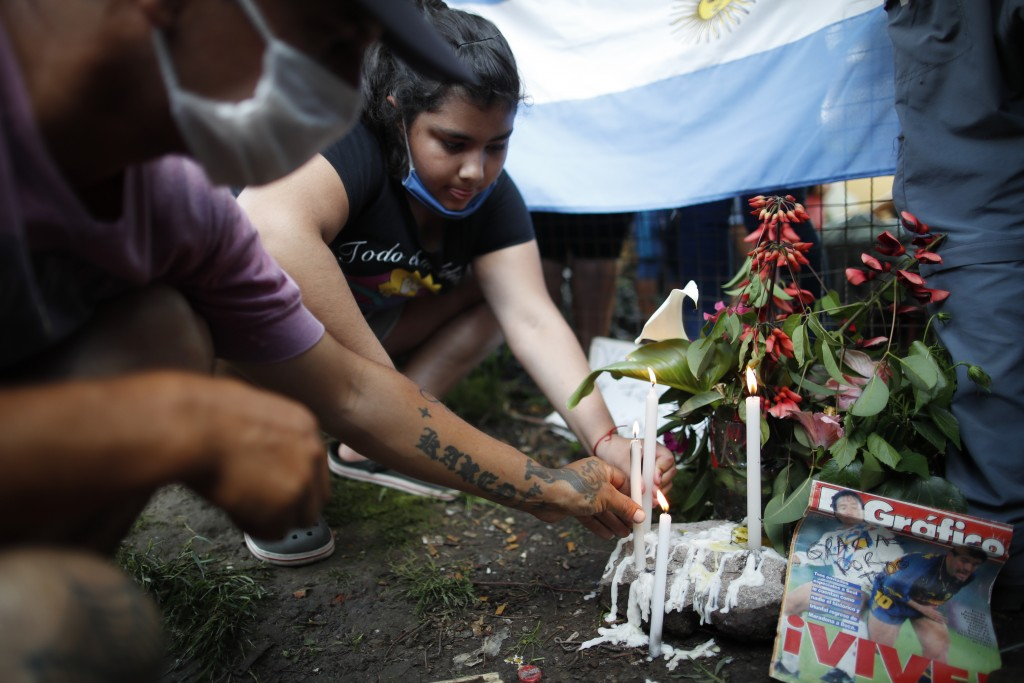 Neighbors light candles at the entrance the house where Diego Maradona was born in the Villa Fiorito neighborhood of Buenos Aires, Argentina, Wednesda...