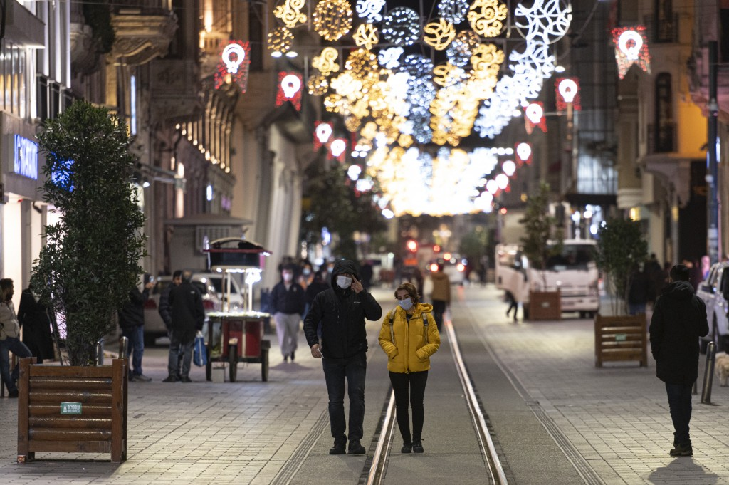 People, wearing masks to help curb the spread of the coronavirus, walk in Istiklal street, the main shopping street in Istanbul, late Wednesday, Nov. ...