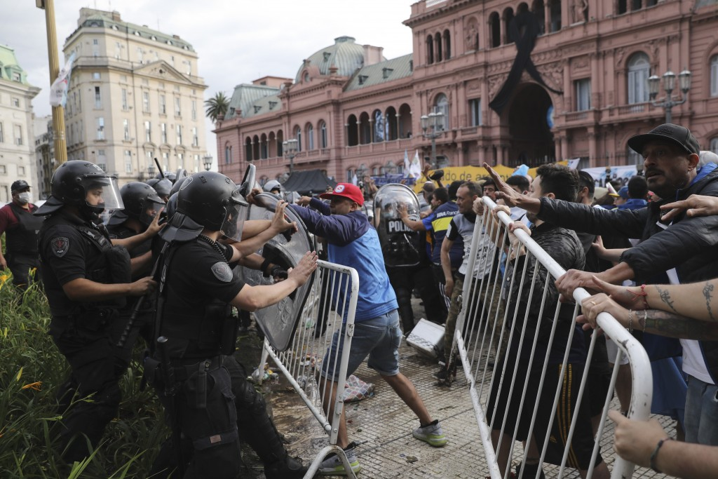 Soccer fans waiting to see Diego Maradona lying in state clash with police outside the presidential palace in Buenos Aires, Argentina, Thursday, Nov. ...