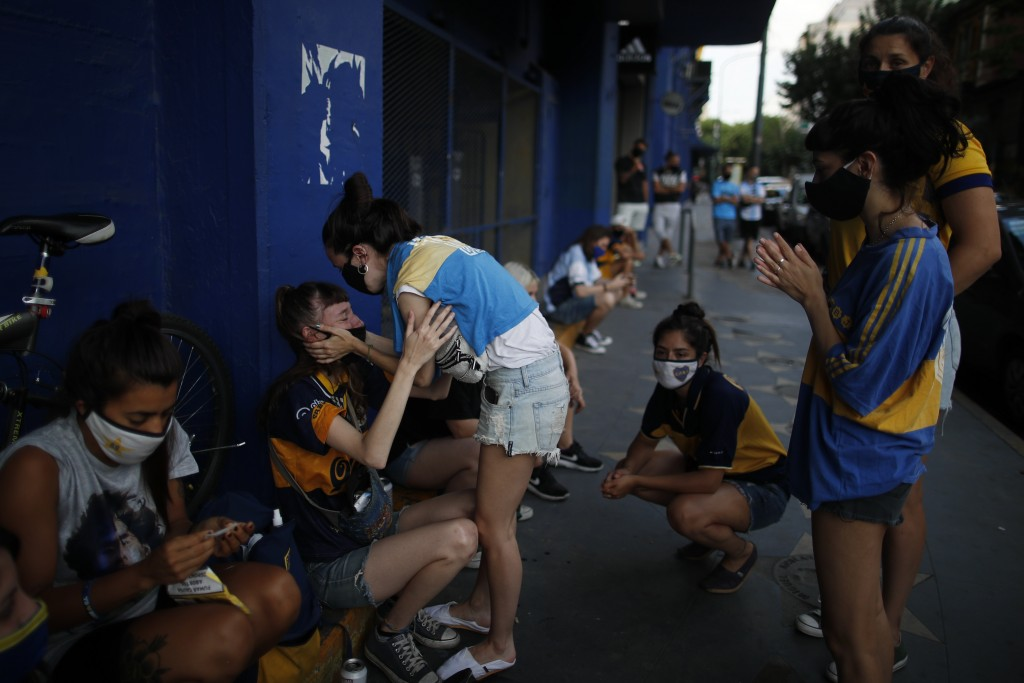 Fans mourn the death of Diego Maradona at the entrance of the Boca Juniors stadium, known as La Bombomera, in Buenos Aires, Argentina, Wednesday, Nov....