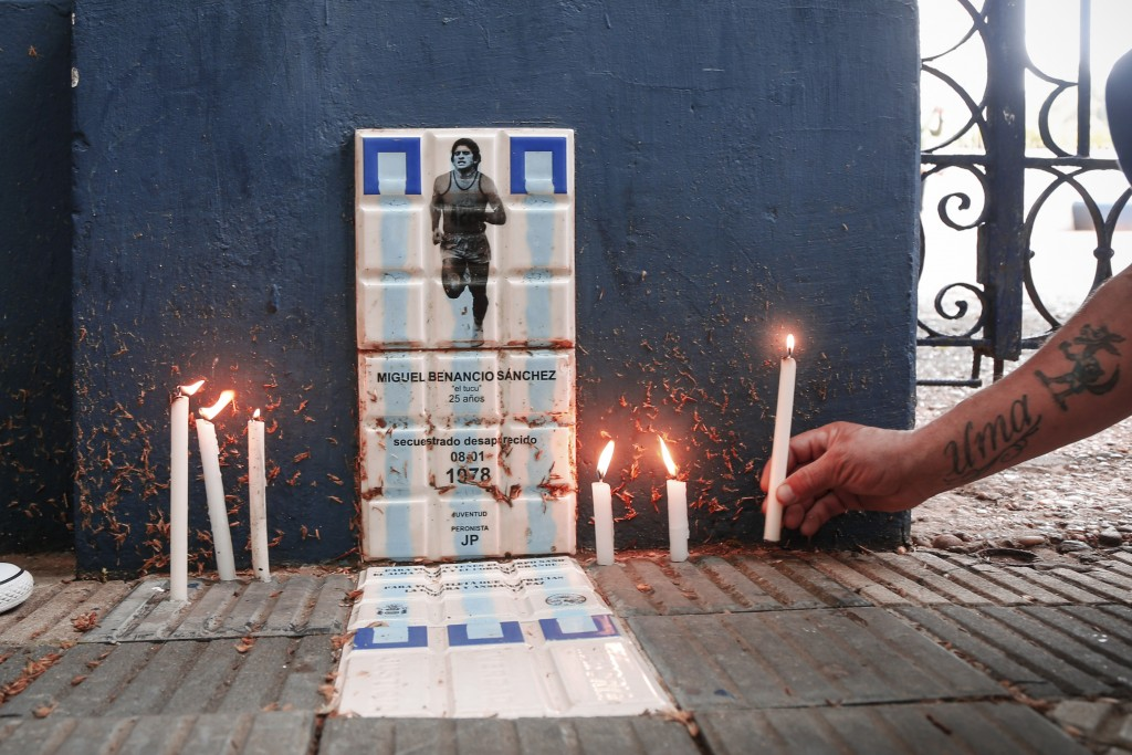 A soccer fan lights candles at the entrance of the home stadium of Gimnasia y Esgrima soccer team, coached by Diego Maradona, in La Plata, Argentina, ...