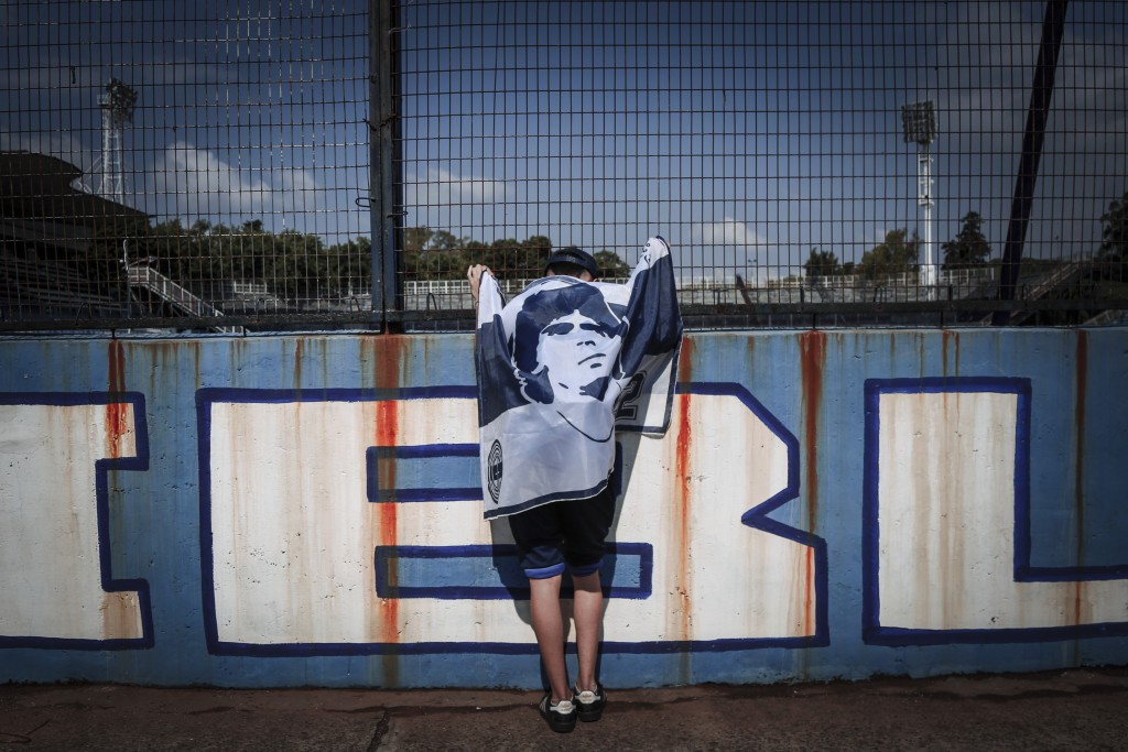 A fan wrapped in a flag with an image of Diego Maradona leans on the fence of the Gimnasia y Esgrima stadium in La Plata, Argentina, Wednesday, Nov. 2...