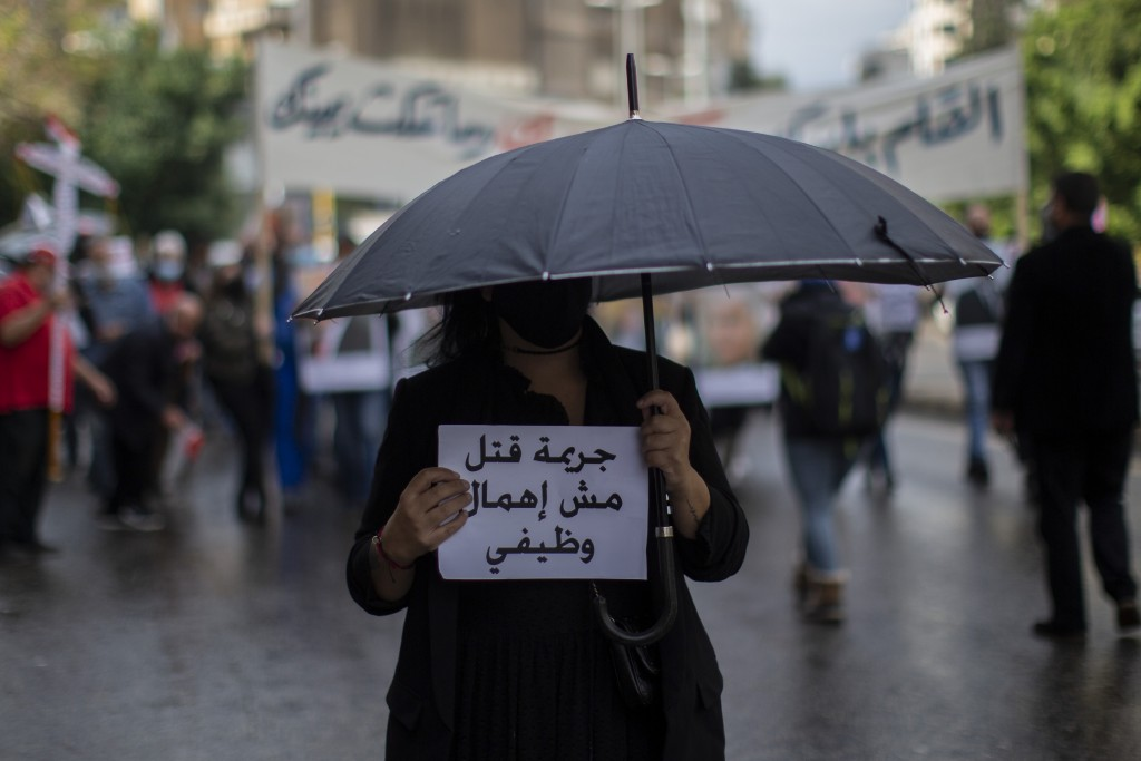 "An anti-government protester holds an Arabic sign that reads: ""It is a criminal murder, not negligence,"" during a protest in Beirut's Ashrafieh distri..."