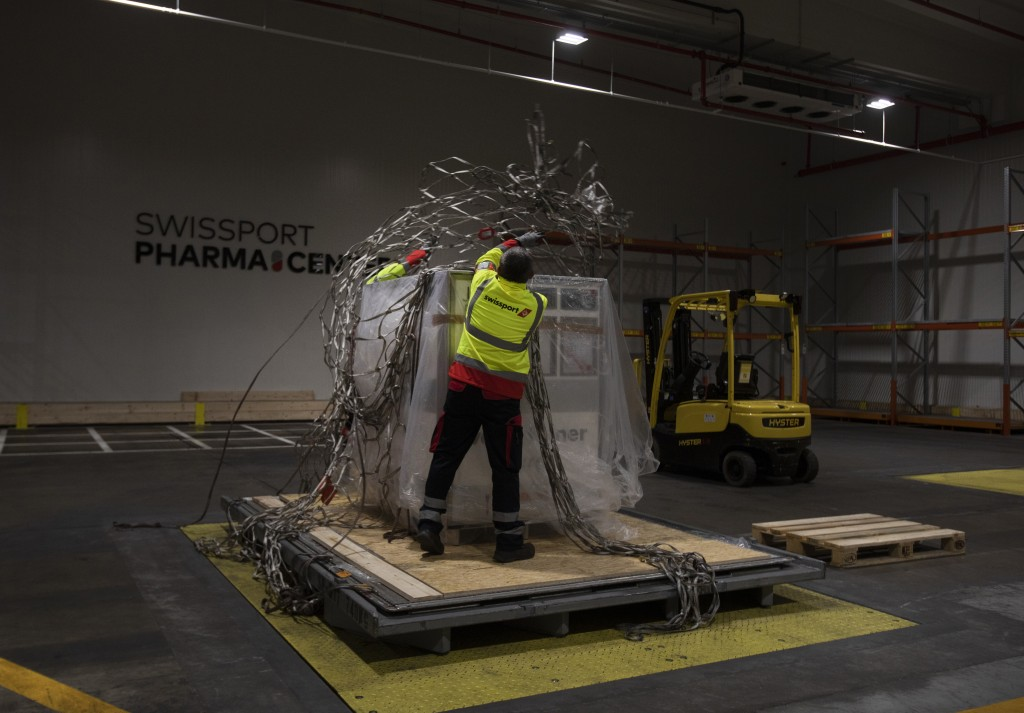 Cargo workers demonstrate the cold chain process for medicines and vaccines as they secure a temperature controlled shipping box in a refrigerated war...
