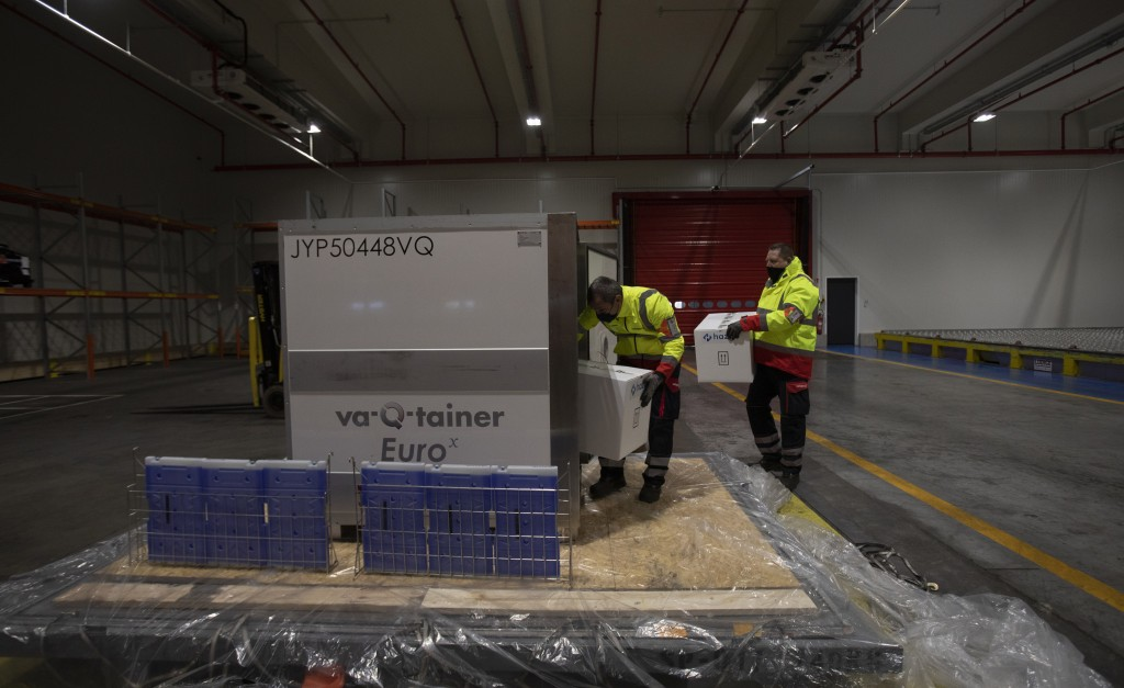 Cargo workers demonstrate the cold chain process for the handling of medicines and vaccines as they place boxes into a temperature controlled shipping...