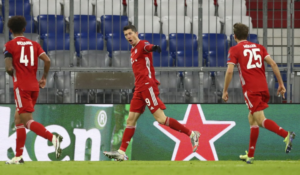 Bayern's Robert Lewandowski, center, celebrates with teammates after scoring his sides first goal during the Champions League Group A soccer match bet...