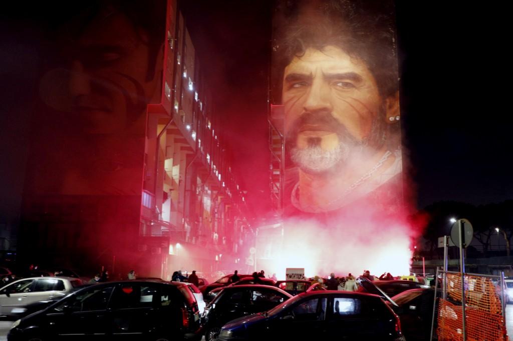 People light flares as they gather under a mural depicting soccer legend Diego Maradona, in Naples, Italy, Wednesday, Nov. 25, 2020. Diego Maradona ha...