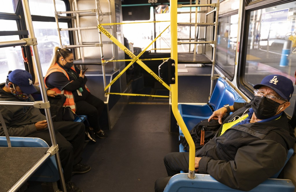 Airport workers take a shuttle bus between terminals at Los Angeles International Airport in Los Angeles, Wednesday, Nov. 25, 2020. Residents were urg...