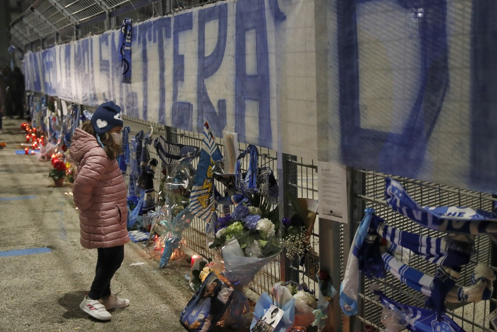 A girl stops and look as people gather outside the San Paolo Stadium to pay their homage to soccer legend Diego Maradona, in Naples, Italy, Wednesday,...