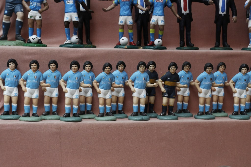 FILE - In this Wednesday, Sept. 18, 2019 file photo, statuettes of soccer legend and former Napoli player Diego Armando Maradona are displayed on the ...
