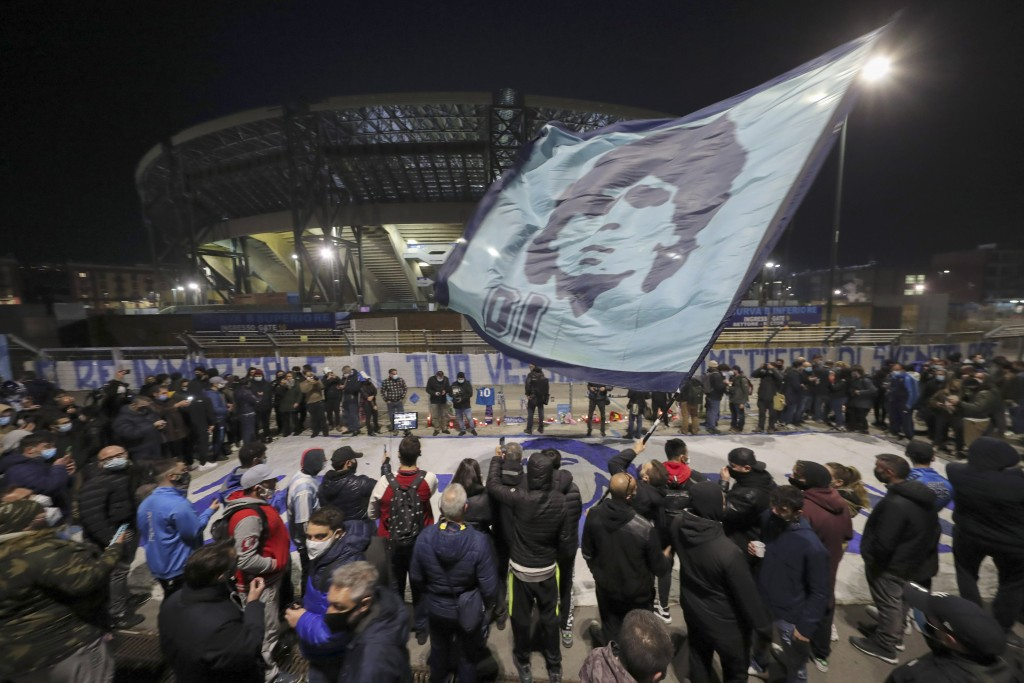 People gather outside the San Paolo Stadium to pay their homage to soccer legend Diego Maradona, in Naples, Italy, Wednesday, Nov. 25, 2020. Diego Mar...