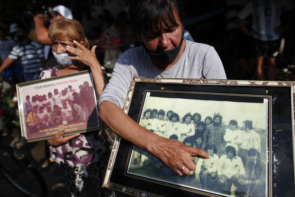 A neighbor points at a young Diego Maradona in a photo where he is lining up with a local soccer team, in front of the house where he was born at the ...