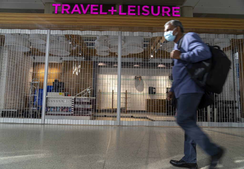 An international traveler walks past a closed store at the Los Angeles International Airport in Los Angeles Wednesday, Nov. 25, 2020. Residents were u...