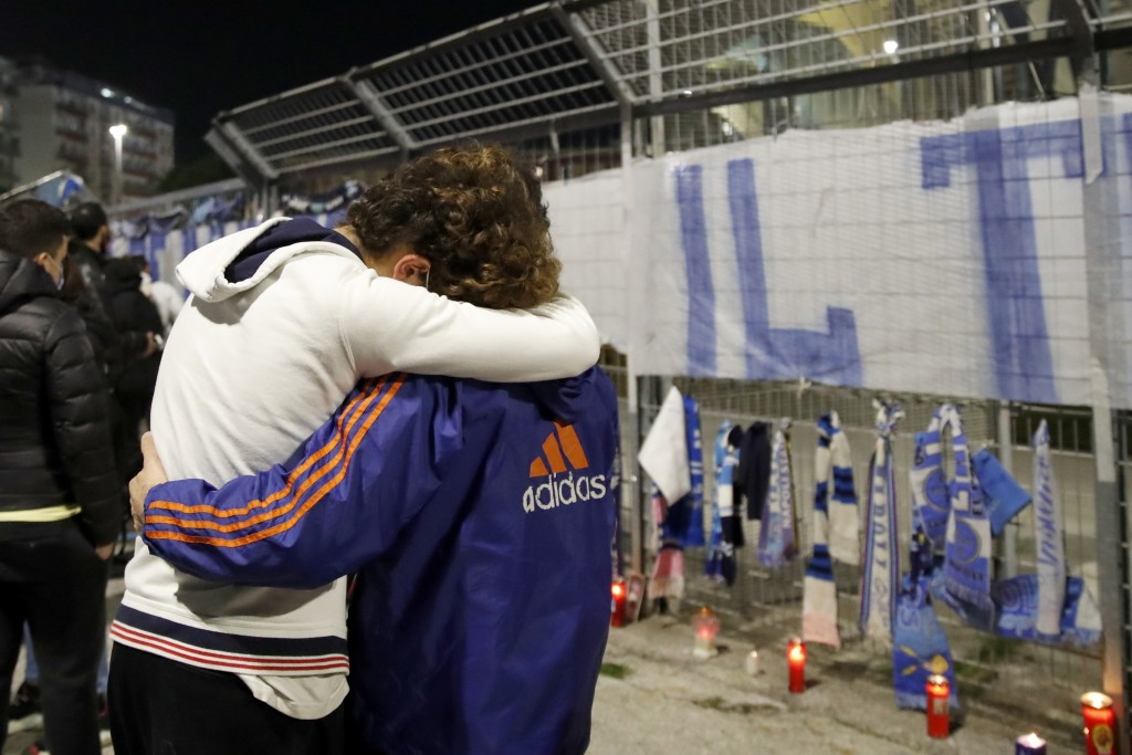 Two supporters hug each other outside the San Paolo Stadium as people gathered and pay their homage to soccer legend Diego Maradona, in Naples, Italy,...